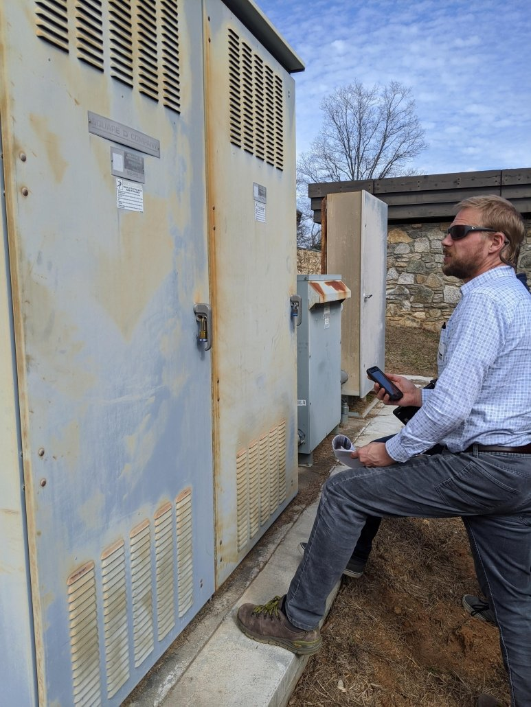 Evan Becka of Pisgah Energy checks out the main distribution panel on a potential solar site.