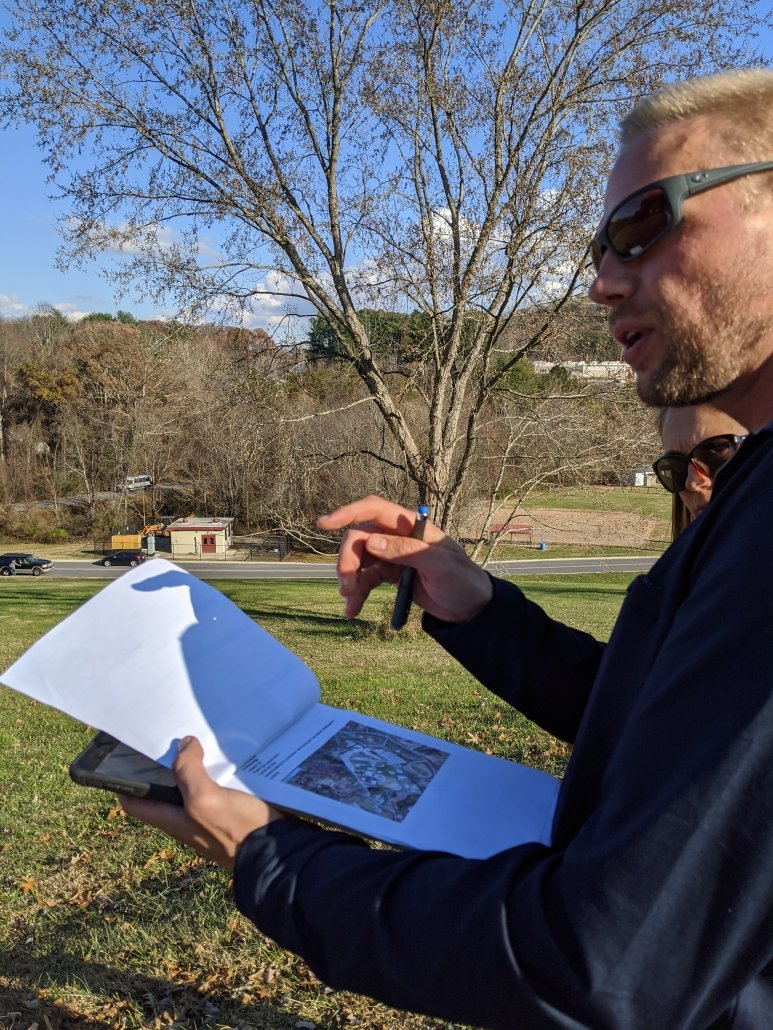 Evan Becka and Alesha Reardon review a potential solar site for Buncombe County Schools.